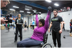 A female wheelchair athlete lifts two weights above her head at the inaugural Ability Workout of the Day