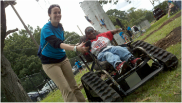 A volunteer helps a child try a motorized all-terrain wheelchair at the Global Abilities Rec Fest