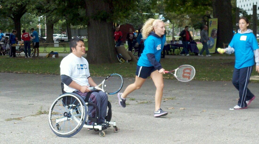 A wheelchair participant and a volunteer play wheelchair tennis at the Global Abilities Rec Fest