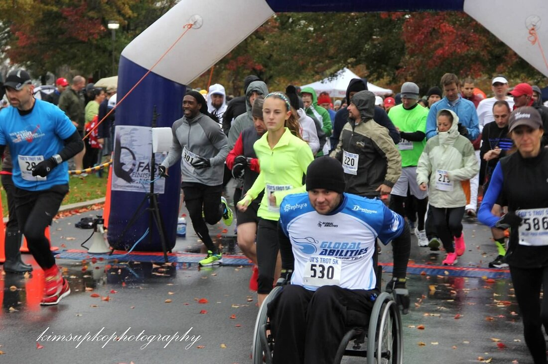 A Global Abilities wheelchair racer leads hundred of competitors at the Brad Fox Memorial 5K race