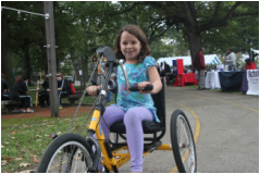 A young girl riding a three-wheeled handcycle at the Philadelphia Rec Fest