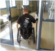 A Global Abilities staff member in a wheelchair enters a building as part of an Accessibility Improvement Program site visit